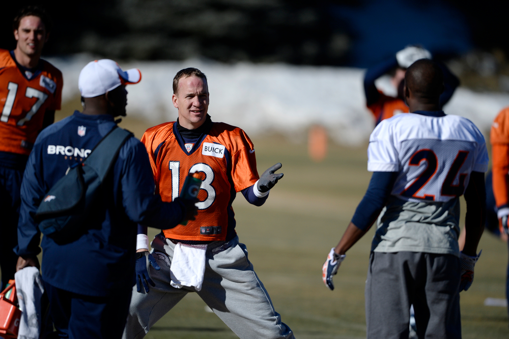. Denver Broncos QB, Peyton Manning, left, and CB, Champ Bailey, talk while stretching during practice at Dove Valley Saturday morning, January 25, 2014. (Photo By Andy Cross / The Denver Post)