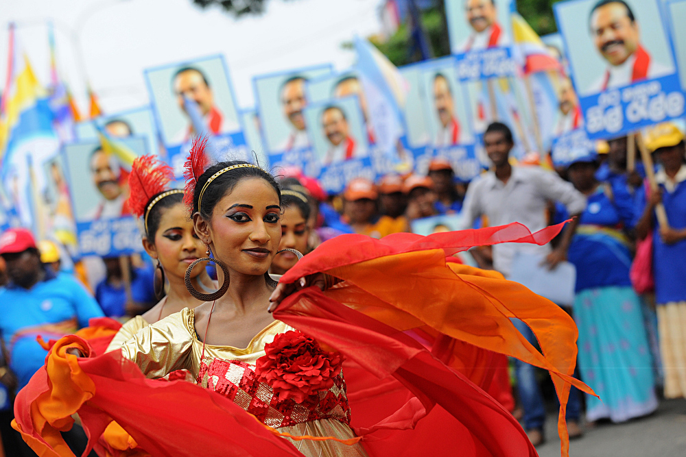 Description of . Sri Lankan dancers look on during a pro-government May Day rally in Colombo May 1, 2013. Sri Lanka tightened security for dozens of labour day rallies in the capital with the opposition using the occasion to focus on sharp increases in electricity and high living costs.  S.KODIKARA/AFP/Getty Images