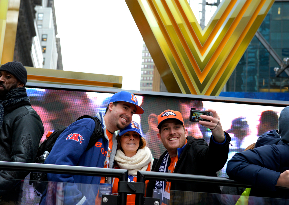 Description of . Broncos fan Allison Delevil, center, is flanked by her fiancé, Steve Johnson, right, and his brother, Michael while making their picture at Times Square in New York, NY January 31, 2014. The NFL has transformed 13 blocks of Broadway into Super Bowl Boulevard before Sundays Super Bowl between the Denver Broncos and Seattle Seahawks. Michael Johnson, of Colorado Springs said,