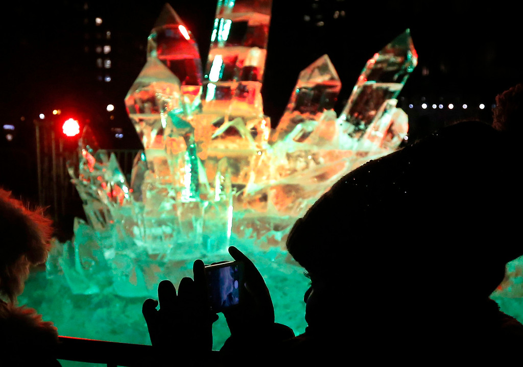 . A woman takes a picture of a colorful ice sculpture during New Year�s Eve festivities in Boston�s Copley Square, Wednesday, Dec. 31, 2014. (AP Photo/Elise Amendola)