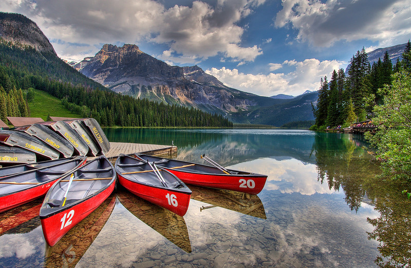 Stock id# 001                                                                                                     Canoes at Emerald Lake  Early morning with calm waters reflecting over Emerald Lake. 5 minutes later the ripple that is just appearing at the top of the water covered the entire lake and my reflections were gone. Timing is so important.