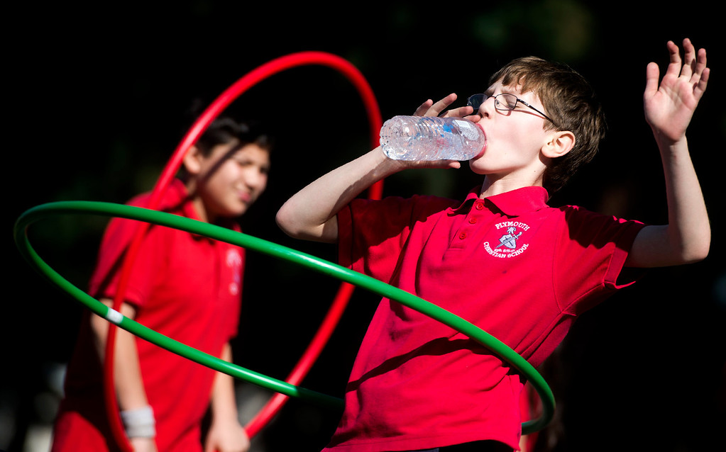 . Ezera Vlad, 9, spins a hula-hoop while drinking water as the fourth grade class exercice at Plymouth Christian School in Whittier on Friday, Feb. 14, 2014. The school held the exercise event to promote good health. (Photo by Watchara Phomicinda/ Whittier Daily News)