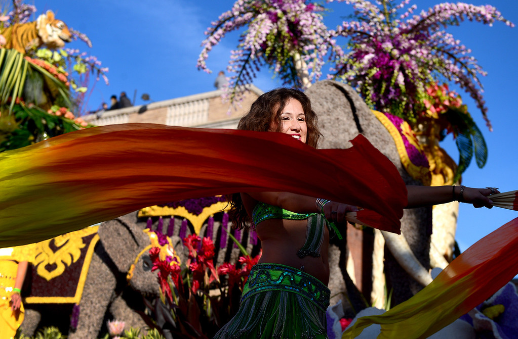 ". A woman dances alongside Dole\'s ""Sunrise at the Oasis\"" float as it heads down Colorado Boulevard during the 125th Rose Parade in Pasadena, CA January 1, 2014. (Photo by Sarah Reingewirtz/Pasadena Star-News)"
