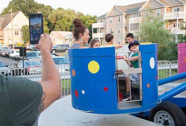 07/26/19 Wesley Bunnell | Staff Marina Janazzo, L, rides the Tubs of Fun with Arabella Volpe, age 4, and Angelo Calandra, age 3, ride the at the first night of the Italian Festival in Southington on Friday night.