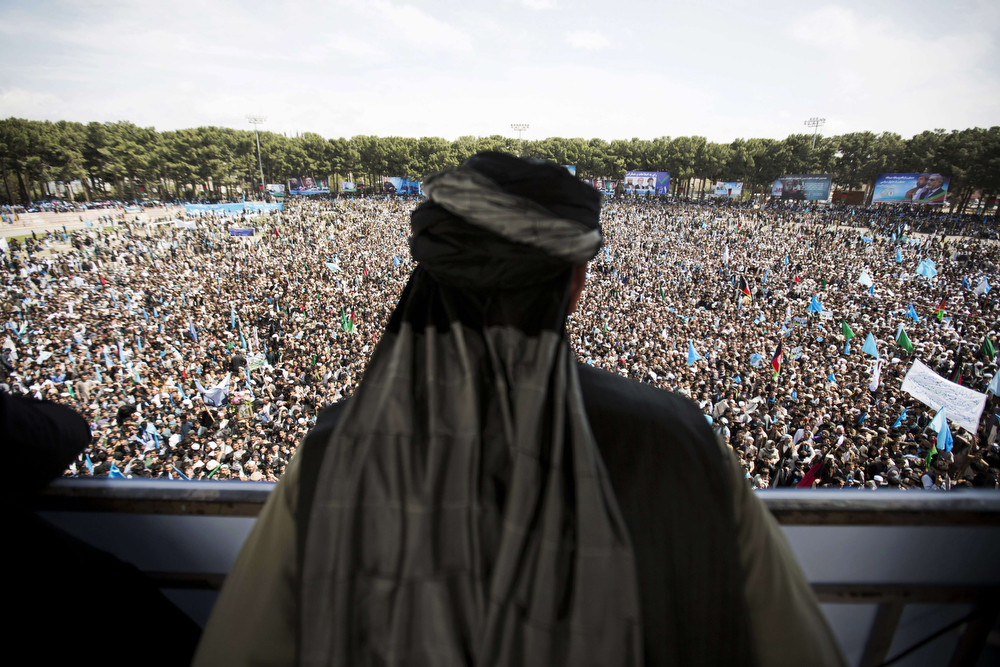 . An Afghan man watches the crowd supporting presidential candidate Abdullah Abdullah during a campaign rally at a stadium in the northwestern city of Herat on April 1, 2014. Afghanistan will vote on April 5 to choose a successor to President Hamid Karzai and to decide the make-up of 34 provincial councils in elections seen as a benchmark of progress since the Taliban were ousted from power in 2001. (BEHROUZ MEHRI/AFP/Getty Images)