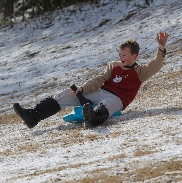 . Jason Buley, 11, slides down a hill in Foster Park on a make shift sled, Wednesday, Dec. 26, 2012, after winter weather covered the area with a layer of snow on Christmas Day. (AP Photo/The Fort Worth Star-Telegram, Rodger Mallison)