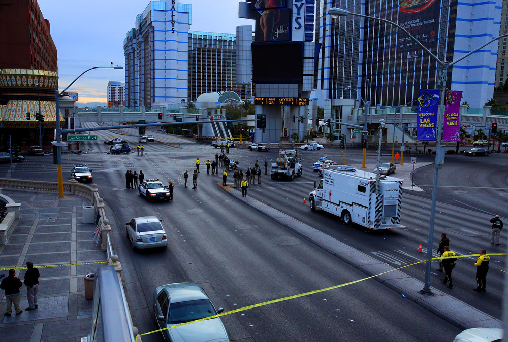 . Law enforcement personal investigate the scene of a mulit-vehicle accident on Las Vegas Blvd. and Flamingo Road Thursday, Feb. 21, 2013. Authorities say a Range Rover opened fire on a Maserati at a stoplight, sending it crashing into a taxi that went up in flames, leaving three people dead and at least six injured. Police were checking with nearby businesses to see whether a previous altercation prompted the car-to-car attack  (AP Photo/Las Vegas Review-Journal, Jeff Scheid)