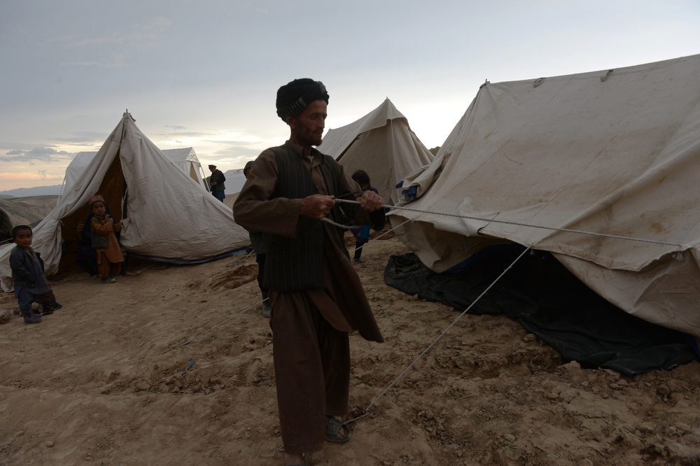 . An Afghan villager erects a relief tent in Argo district of Badakhshan province on May 3, 2014 after a massive landslide May 2 buried a village. Rescue teams abandoned the search for survivors May 3 after a landslide buried a hillside village in northern Afghanistan, killing at least 300 people under a fast-moving tide of rock and mud. Officials said that the final death toll could rise as high as 500 after Friday\'s disaster, updating earlier information that 2,500 people were feared dead. (SHAH MARAI/AFP/Getty Images)
