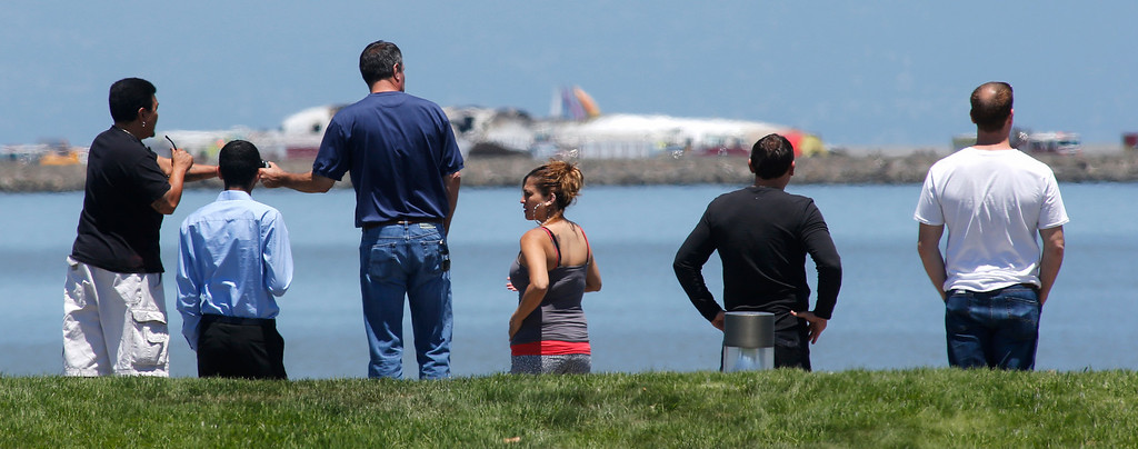 . People check out the Asiana Airlines Boeing 777 that crashed while landing at San Francisco International Airport on Saturday, July 6, 2013. (John Green/Bay Area News Group)