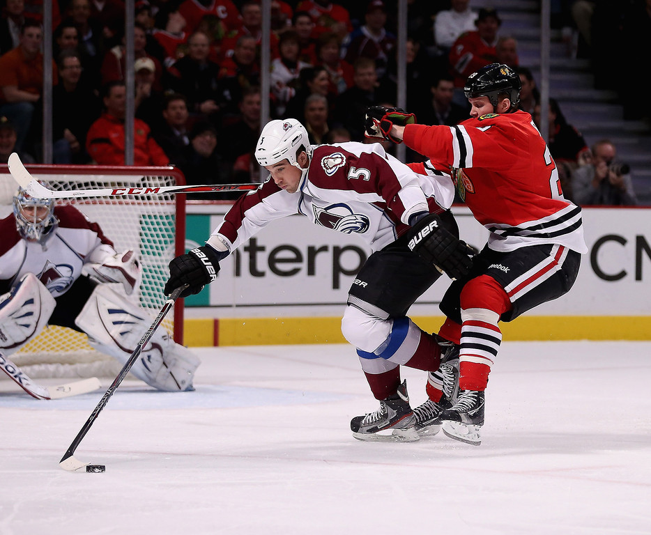 . Shane O\'Brien #5 of the Colorado Avalanche controls the puck under pressure from Bryan Bickell #29 of the Chicago Blackhawks at the United Center on March 6, 2013 in Chicago, Illinois.  (Photo by Jonathan Daniel/Getty Images)