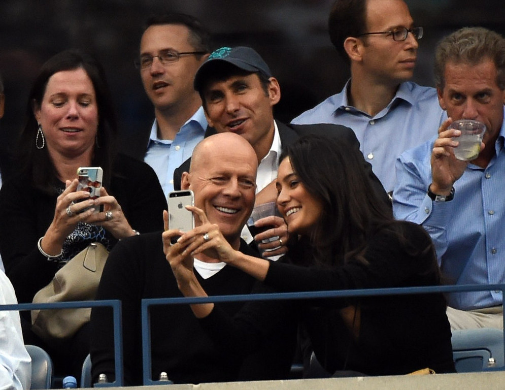 . Bruce Willis and his wife Emma Heming-Willis watch the match between Marin Cilic of Croatia and Kei Nishikori of Japan during the US Open 2014 men\'s singles finals match at the USTA Billie Jean King National Center September 8, 2014  in New York. TIMOTHY A. CLARY/AFP/Getty Images