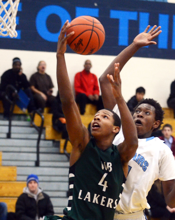 . West Bloomfield\'s #4 Trishton Jackson goes up for a layup that gets blocked by Waterford Mott\'s #11 Austin Sherrell during their game at Waterford Mott High School, Thursday December 12, 2013. (Vaughn Gurganian-The Oakland Press)