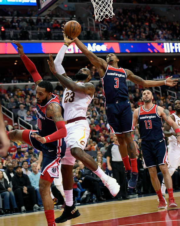 . Cleveland Cavaliers forward LeBron James (23) goes to the basket against Washington Wizards guard Bradley Beal (3), forward Mike Scott, left, and Washington Wizards center Marcin Gortat (13), of Poland, during the first half of an NBA basketball game, Sunday, Dec. 17, 2017, in Washington. (AP Photo/Nick Wass)