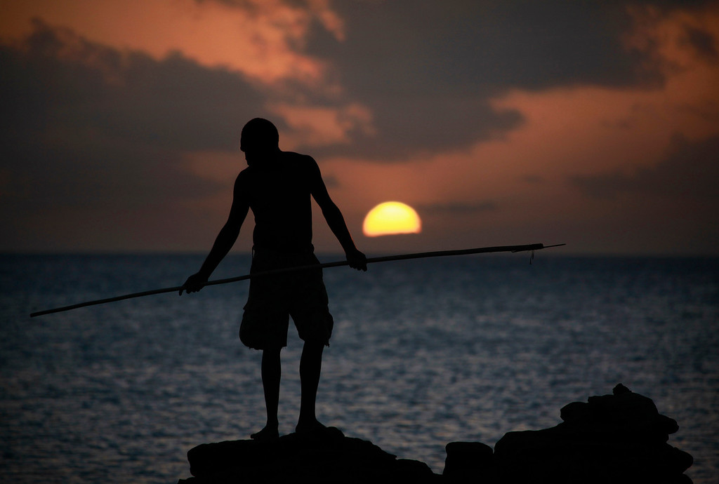 . Lance-corporal Vinnie Rami, an indigenous soldier from Australia\'s North West Mobile Force (NORFORCE) unit, hunts for fish with a spear as the sun sets on Wigram Island, part of the English Company Islands, located inside Arnhem Land in the Northern Territory July 18, 2013. NORFORCE is a surveillance unit that employs ancient Aboriginal skills to help in the seemingly impossible task of patrolling the country\'s vast northwest coast. NORFORCE\'s area of operations is about 1.8 million square km (700,000 square miles), covering the Northern Territory and the north of Western Australia. Aboriginal reservists make up a large proportion of the 600-strong unit, and bring to bear their knowledge of the land and the food it can provide. Fish, shellfish, turtle eggs and even insects supplement rations during the patrol, which is on the lookout for illegal foreign fishing vessels and drug smugglers, as well as people smugglers from neighboring Indonesia.  Picture taken July 18, 2013.   REUTERS/David Gray