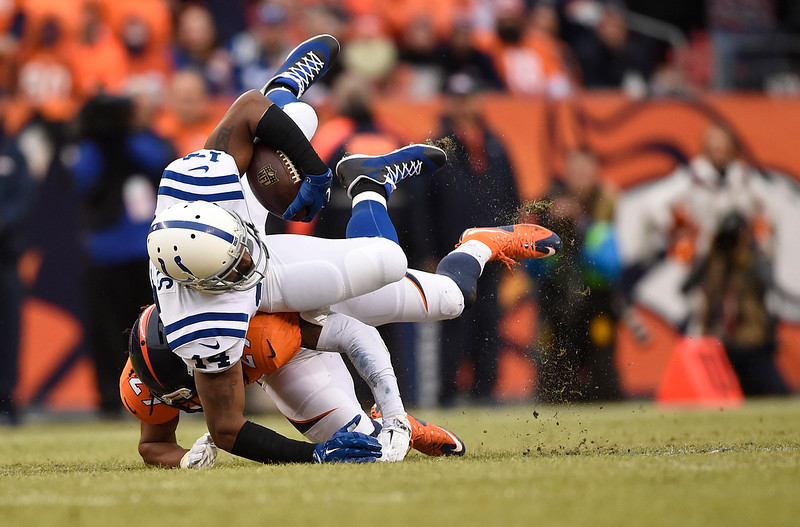 . Hakeem Nicks (14) of the Indianapolis Colts makers a catch for a first down and is taken down by Bradley Roby (29) of the Denver Broncos in the first quarter. The Denver Broncos played the Indianapolis Colts in an AFC divisional playoff game at Sports Authority Field at Mile High in Denver on January 11, 2015. (Photo by AAron Ontiveroz/The Denver Post)