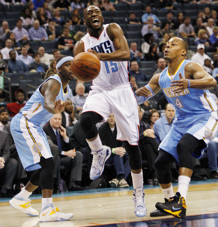 . Charlotte Bobcats guard Kemba Walker (15) loses control of the ball as he drives pas Denver Nuggets guard Randy Foye, right, during the first half of an NBA basketball game in Charlotte, N.C., Monday, March 10, 2014. (AP Photo/Nell Redmond)