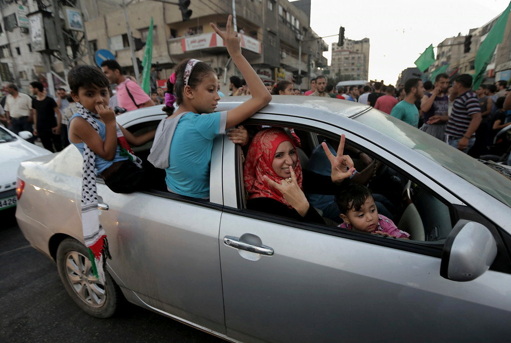 . A Palestinian family flashes victory signs as they celebrate the cease-fire between Palestinians and Israelis at the main rood in Gaza, in the northern Gaza Strip, Tuesday, Aug. 26, 2014.  Israel and Hamas agreed Tuesday to an open-ended cease-fire, halting a seven-week war that killed more than 2,200 people, the vast majority Palestinians, left tens of thousands in Gaza homeless and devastated entire neighborhoods in the blockaded territory.  (AP Photo/Adel Hana)