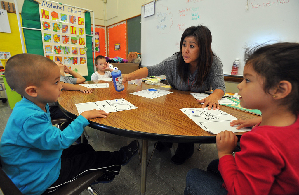 . Pre-school teacher Aimee Iwasaki pours paint out for her students George Evver Ibarra, left, and Aimee Hernandez during class at Buffum Total Learning Center in Long Beach, CA on Wednesday, October 9, 2013.  Beginning next week, Buffum, a pre-school for special needs students, will start a program called Typical Peers which will have their students with disabilities working side by side with normally developing students. (Photo by Scott Varley, Daily Breeze)