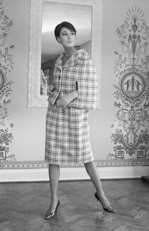. The little cape, just right for the new soft fashions, tops an easy skirt in a three-piece suit of airy, lightweight British wool in a muted lilac, green and beige plaid, shown Feb. 26, 1964. The sleeveless overblouse is in coral linen, by Burke-Amey. (AP Photo/Dan Grossi)