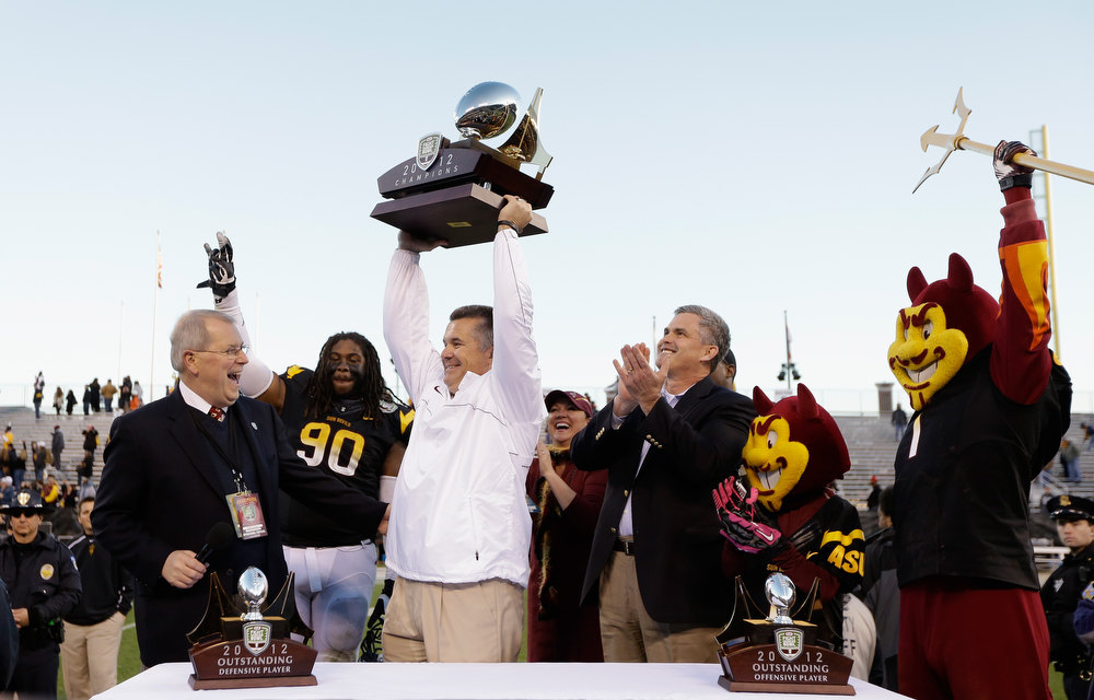 Description of . Head coach Todd Graham of the Arizona State Sun Devils lifts the trophy after they beat the Navy Midshipmen in the Kraft Fight Hunger Bowl at AT&T Park on December 29, 2012 in San Francisco, California.  (Photo by Ezra Shaw/Getty Images)