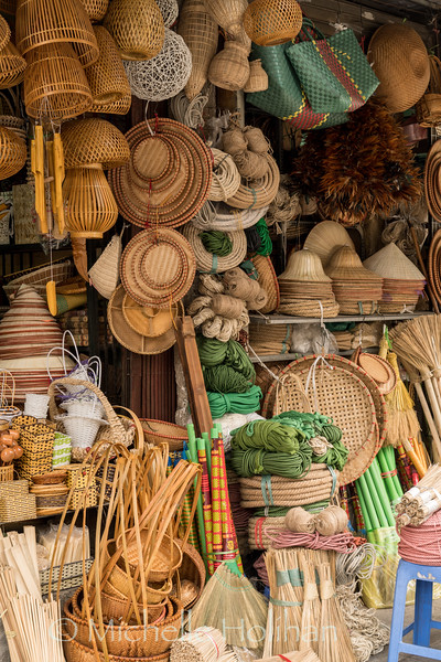 Brooms, baskets and hats for sale at a stall in the Dong Xuan Market, Hanoi, Vietnam