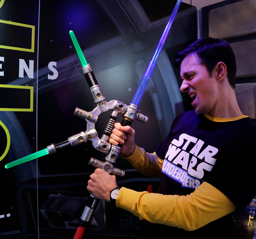 . FILE - In this Saturday, Feb. 14, 2015, file photo, Jeff Wolf demonstrates the Star Wars Bladebuilders Jedi Master Lightsaber at the Hasbro showroom at the North American International Toy Fair,  in New York. Hasbro�s 2016 first-quarter performance topped Wall Street�s view, bolstered by strong sales of �Star Wars,� Disney Princess and �Frozen� merchandise, the company reported Monday, April 18, 2016. (AP Photo/Mark Lennihan, File)