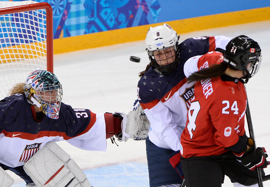 . The puck flies past US Megan Bozek (C) during the Women\'s Ice Hockey Group A match between Canada and USA at the Sochi Winter Olympics on February 12, 2014 at the Shayba Arena. AFP PHOTO / JONATHAN NACKSTRAND/AFP/Getty Images