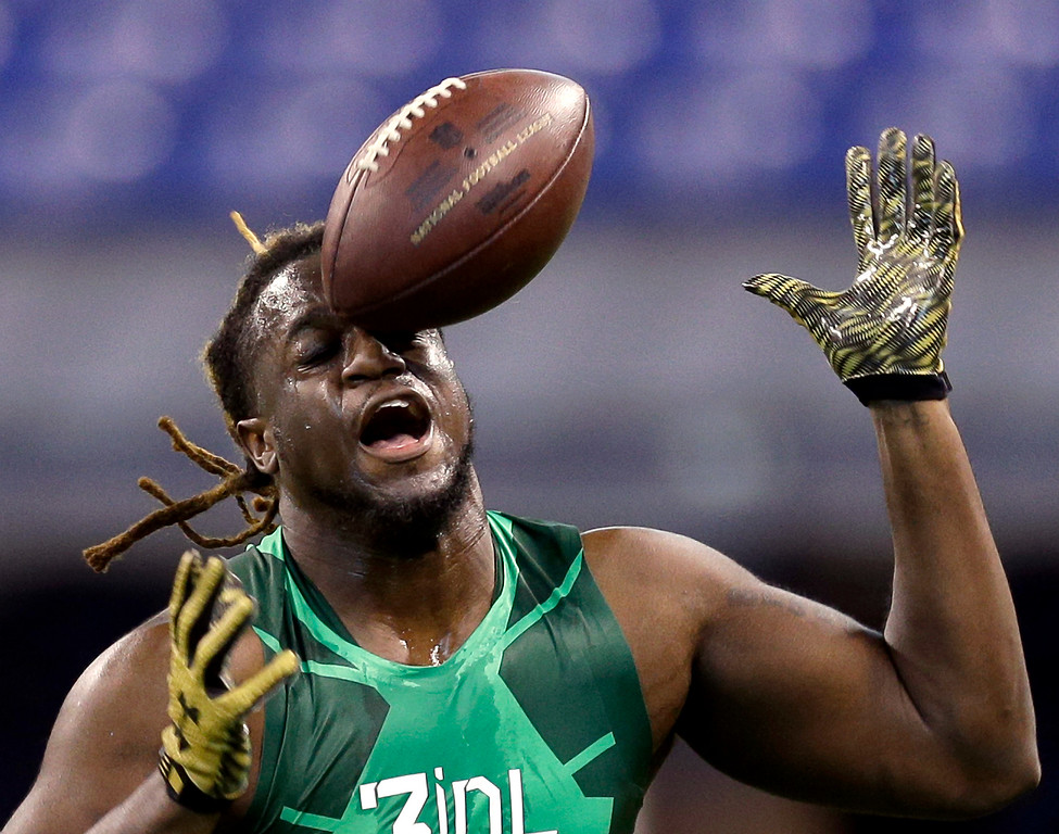 . A football hits defensive lineman Tavaris Barnes while bobbling a pass as he runs a drill at the NFL football scouting combine in Indianapolis, Sunday, Feb. 22, 2015. (AP Photo/David J. Phillip)