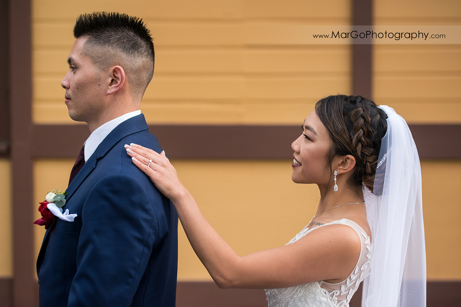 bride tapping groom's arm during first look at train station near Sunol's Casa Bella