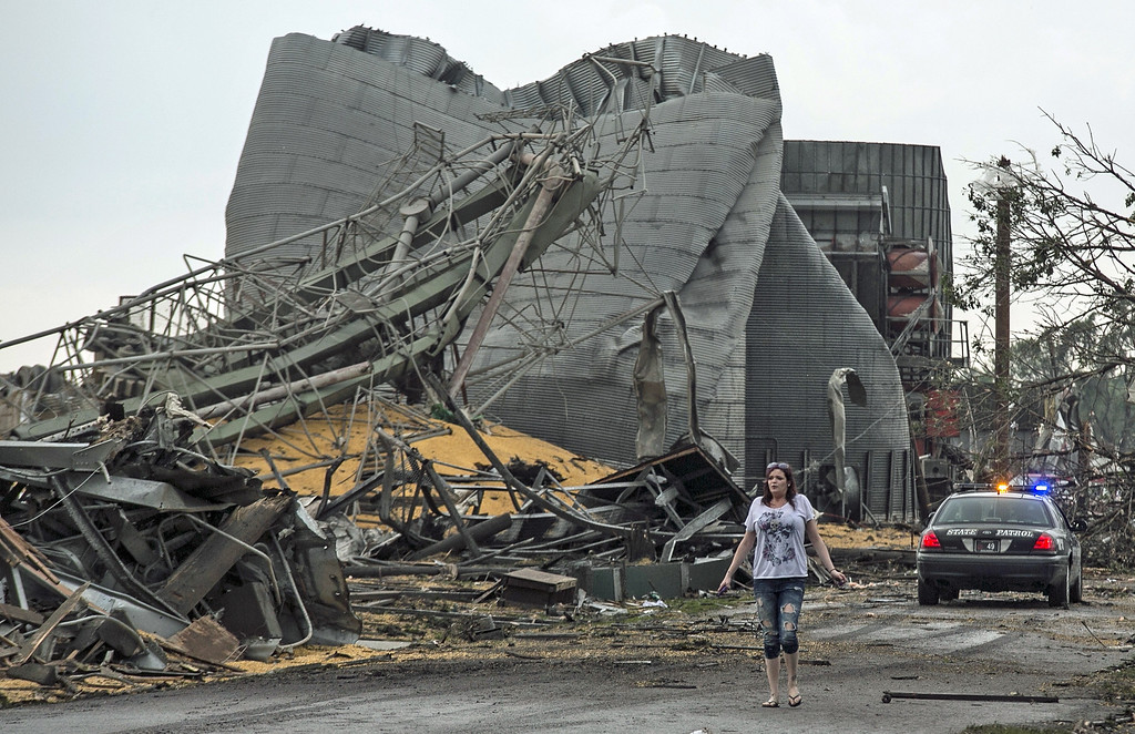 . A woman walks down Black Hills Trail road in Pilger, Neb., Monday, June 16, 2014. At least one person is dead and at least 16 more are in critical condition after two massive tornadoes swept through northeast Nebraska on Monday. (AP Photo/Mark \'Storm\' Farnik)
