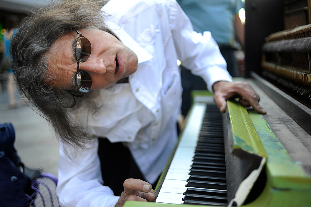""". Coming from a long line of family musicians, Nick Juele, a piano rebuilder and player, inspects the keys on a broken 16th Street Mall piano, on Friday morning, June 18, 2010. \""""Some people have no respect for communal property,\"""" Juele said.  (Diego James Robles, The Denver Post)"""