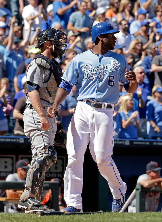. Kansas City Royals\' Lorenzo Cain (6) runs home past Detroit Tigers catcher Bryan Holaday to score on a single by Billy Butler during the first inning of a baseball game Sunday, Sept. 21, 2014, in Kansas City, Mo. (AP Photo/Charlie Riedel)