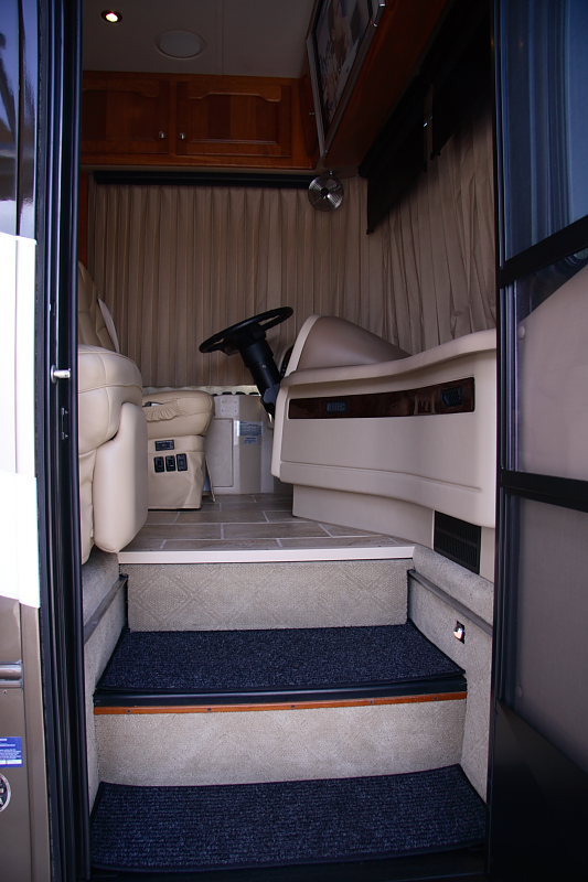 Entrance into the vehicle is comprised of 2 steps outside (not shown) and 2 steps inside. Carpet treads are removable for cleaning and a night light is included.  The entrance door has a screen door on the inside.  An automatic floor slide covers the stairs so the passenger has a place to put their feet during travel.
