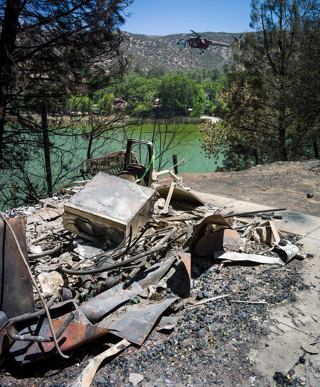 . One of five homes destroyed along East Lake Shore drive next to Lake Hughes lies in rubble as water dropping helicopter moves in to collect water from the lake to drop on the Power House fire which is still burning in the Angeles Forest.   Photo by David Crane/Los Angeles Daily News