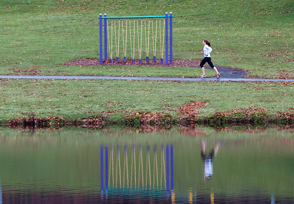 11/13/18 Wesley Bunnell | Staff Reflections of a jogger and work out equipment at Stanley Quarter Park on a cold and wet Tuesday afternoon.