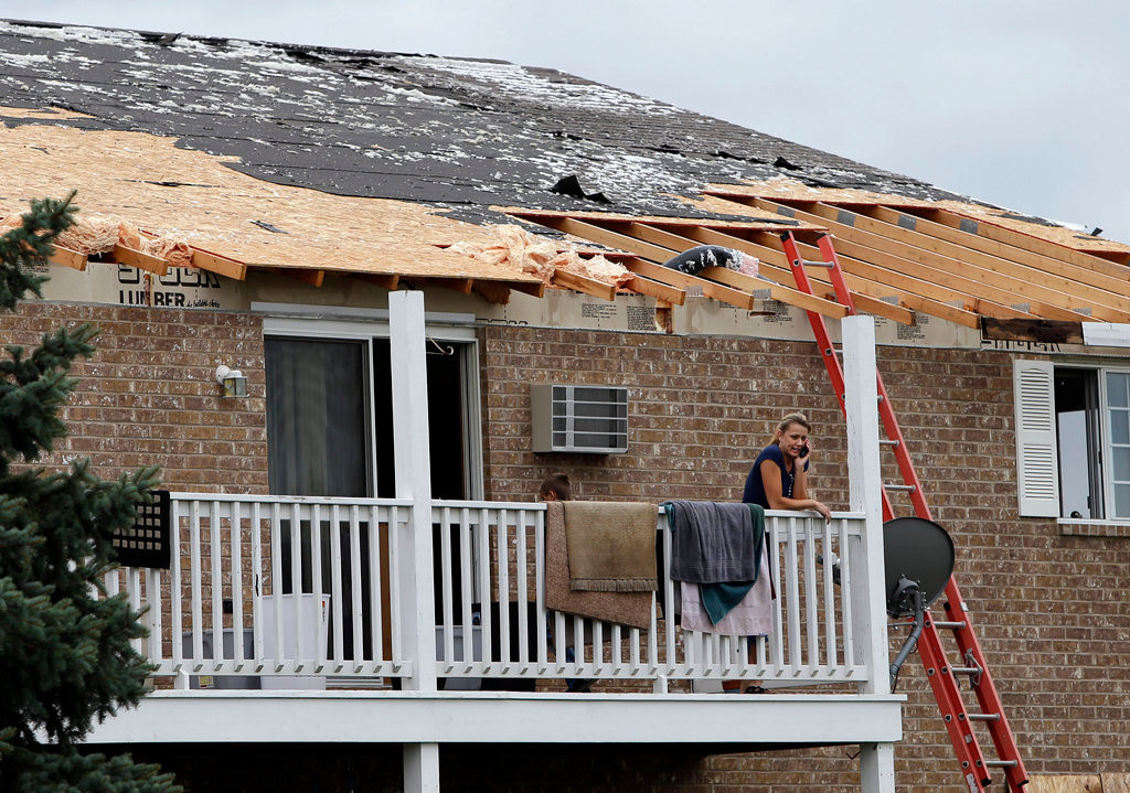 . A resident of a Hortonville, Wis., apartment building stands on her balcony after the roof to the complex was damaged by severe thunderstorms. (AP Photo/The Post-Crescent, Sharon Cekada)