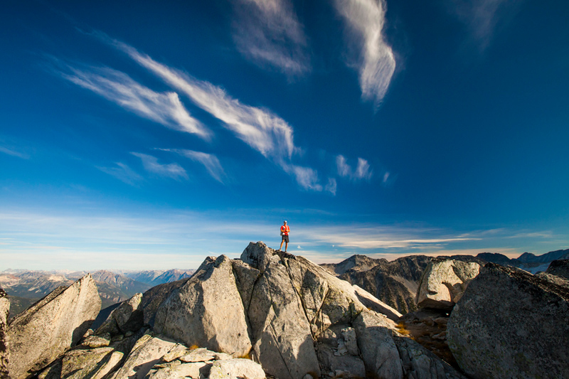 A backpacker stands on top of a rocky summit near Whistler, British Columbia, Canada.