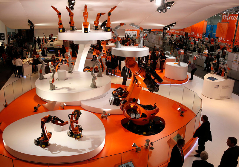 . Visitors watch different sized industrial robots by KUKA at the Hanover Messe on the first day of the industrial trade fair, in Hanover April 8, 2013. The Hanover fair runs from April 8 -12. REUTERS/Fabrizio Bensch
