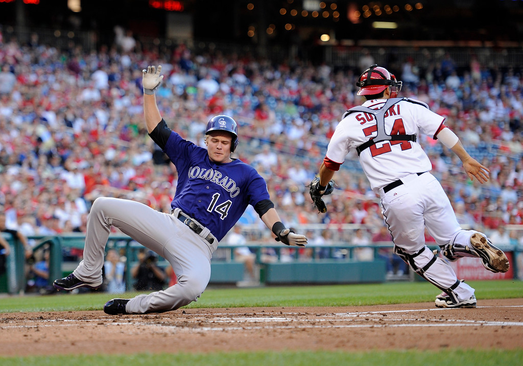 . Colorado Rockies\' Josh Rutledge (14) comes in to score on a single by DJ LeMahieu during the third inning of a baseball game against Washington Nationals catcher Kurt Suzuki (24), Friday, June 21, 2013, in Washington. (AP Photo/Nick Wass)