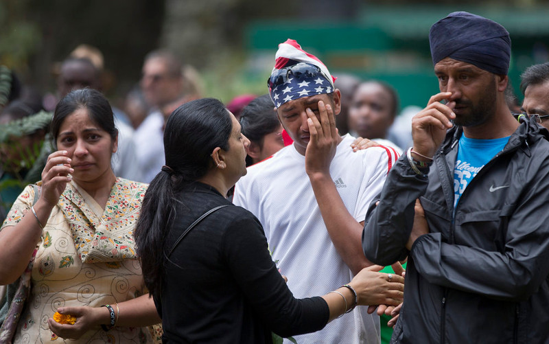 . Relatives of the victims of the Westgate Mall attack prepare to lay flowers and remember, at the Amani Garden memorial site in the Karura Forest in Nairobi, Kenya Sunday, Sept. 21, 2014. Kenya is marking one year since four gunmen stormed the upscale Westgate Mall in Nairobi, killing 67 people, and a memorial plaque with the names of the victims was unveiled at the popular forest on the edge of the city. (AP Photo/Ben Curtis)