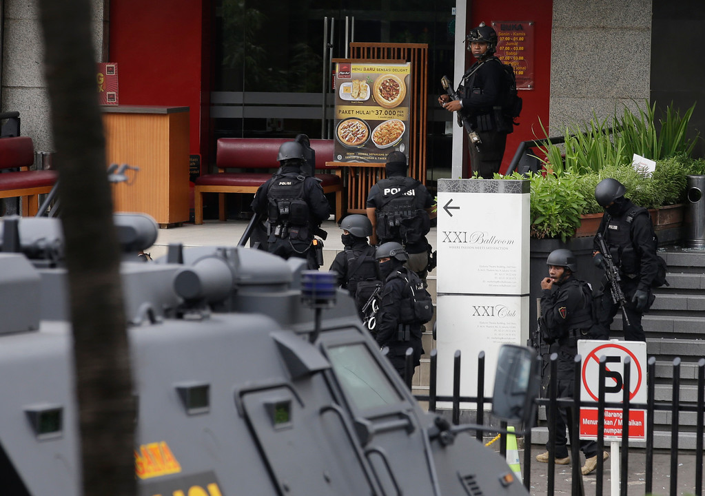 . Police officers take their position outside a Pizza Hut restaurant next door to a Starbucks cafe which was attacked in Jakarta, Indonesia Thursday, Jan. 14, 2016. Attackers set off explosions at the cafe in a bustling shopping area in Indonesia\'s capital and waged gunbattles with police Thursday, leaving bodies in the streets as office workers watched in terror from high-rise windows. (AP Photo/Achmad Ibrahim)