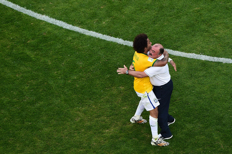 . Brazil\'s defender Marcelo (L) celebrates with a staff member at the end of the penalty shootout after the extra time in the round of 16 football match between Brazil and Chile at The Mineirao Stadium in Belo Horizonte during the 2014 FIFA World Cup on June 28, 2014. (FRANCOIS XAVIER MARIT/AFP/Getty Images)