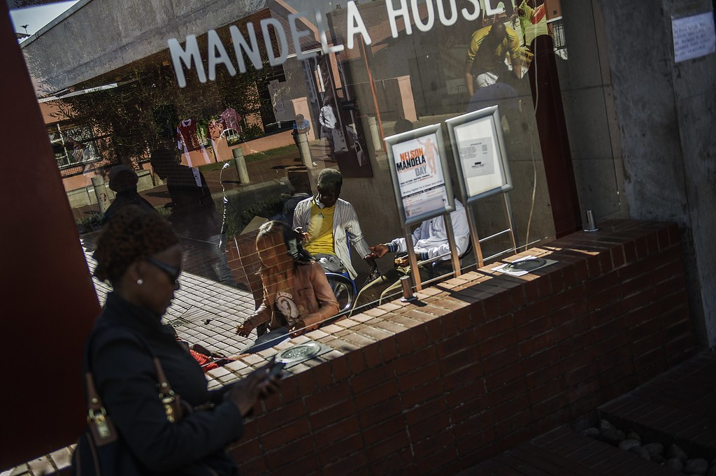 . South African youth sit in the Soweto Mandela House yard as various activities marking International Mandela Day take place in front of the house turned museum of the late global Icon Nelson Mandela on July 18, 2014 in Johannesburg. Mandela Day is a global call to action that celebrates the idea that each individual has the power to transform the world, the ability to make an impact. Nelson Mandela International Day (or Mandela Day) is an annual international day in honour of Nelson Mandela, celebrated each 18 July (on Mandela\'s birthday). The day was officially declared by the United Nations in November 2009, with the first UN Mandela Day held on 18 July 2010. AFP PHOTO/GIANLUIGI GUERCIA        (Photo credit should read GIANLUIGI GUERCIA/AFP/Getty Images)