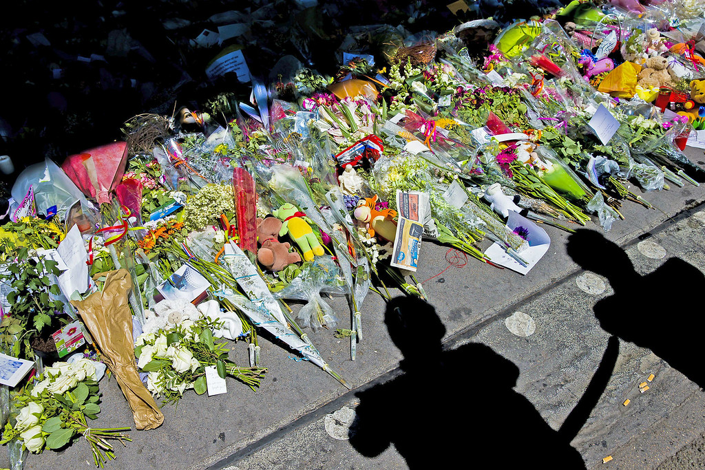 . This photo shows the shadows of peopLe looking at flowers placed in remembrance for the victims of the MH17 plane crash at Schiphol Airport, near Amsterdam, on July 23, 2014. The remains of 40 victims from downed Malaysia Airlines flight MH17 headed on July 23 from eastern Ukraine to the Netherlands aboard two planes. Dutch royals were due to meet the planes alongside grieving relatives and representatives from the 11 countries that had citizens among the 298 on board MH17. AFP PHOTO / ANP / SANDER KONING /AFP/Getty Images