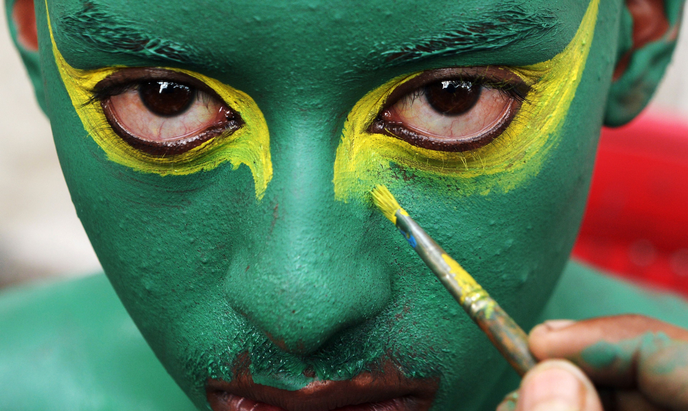 . An Indian football fan has his face painted in the colours of the Brazilian flag as he prepares to cheer on Brazil\'s national football team in Kolkata on June 28, 2014. (DIBYANGSHU SARKAR/AFP/Getty Images)