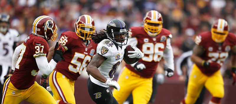 . Baltimore Ravens receiver Torrey Smith (C) is chased by the Washington Redskins defense in the first half of their NFL football game in Landover, Maryland December 9, 2012.     REUTERS/Gary Cameron   (UNITED STATES - Tags: SPORT FOOTBALL)