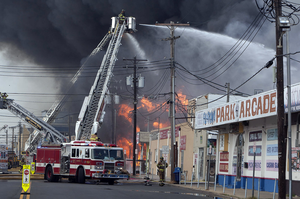 . Firefighters battle a fire on the Seaside Heights, N.J. boardwalk Thursday, Sept. 12, 2013. The fire started in the vicinity of an ice cream shop and burned several blocks of boardwalk and businesses in a town that was still rebuilding from damage caused by Superstorm Sandy. (AP Photo/The Asbury Park Press, Bob Bielk)
