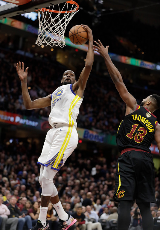 . Golden State Warriors\' Kevin Durant grabs a rebound next to Cleveland Cavaliers\' Tristan Thompson during the second half of Game 3 of basketball\'s NBA Finals, Wednesday, June 6, 2018, in Cleveland. (AP Photo/Tony Dejak)