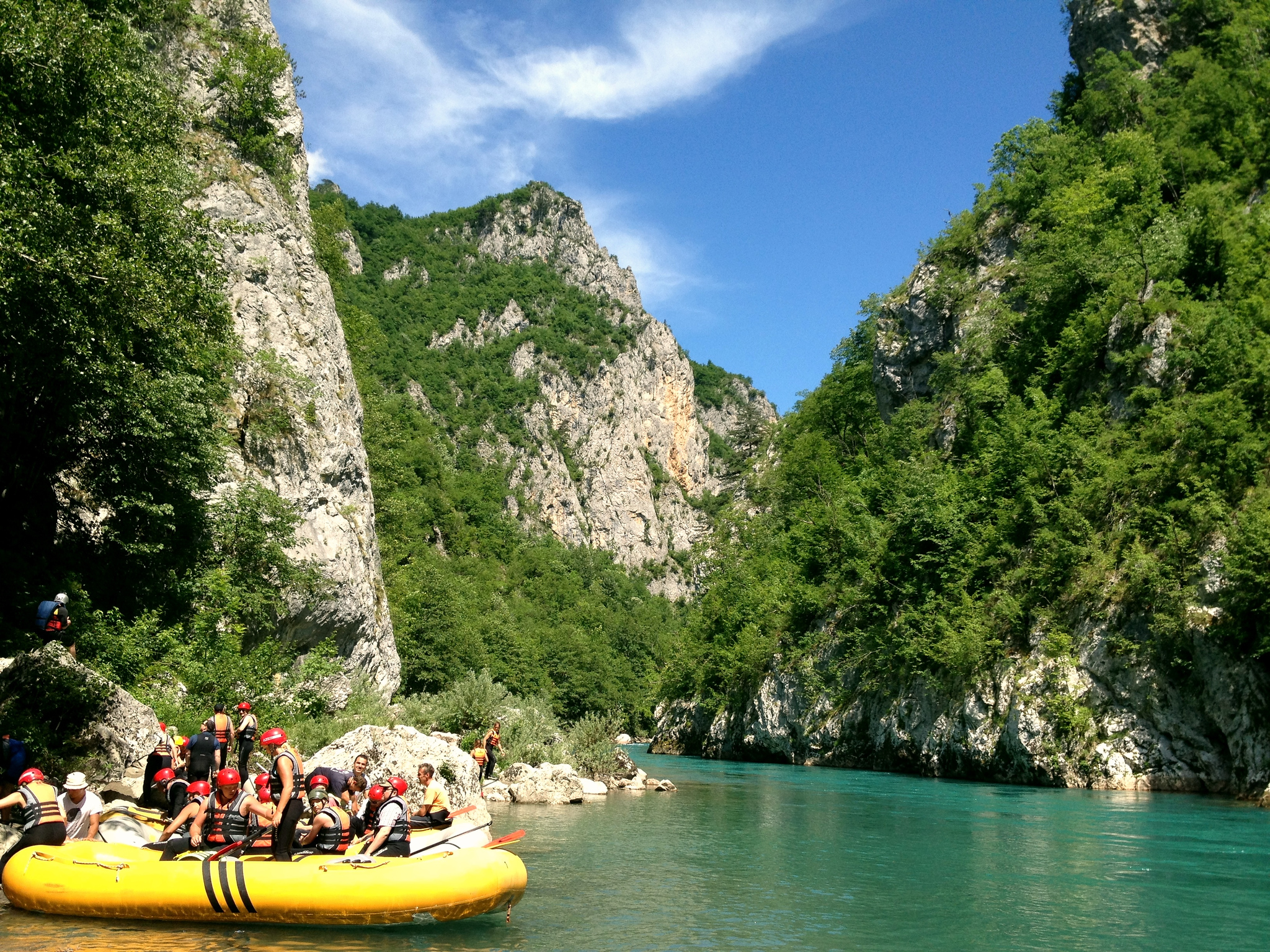 A yellow raft parking in the middle of the green Tara river, surrounded by limestone cliffs and trees.
