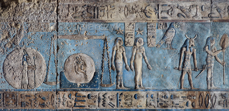 """[EGYPT 29589] 'Libra and Virgo on astronomical ceiling at Dendera.'  Scales and a woman holding an ear of corn portray the zodiac  signs Libra and Virgo on the astronomical ceiling in the outer hypostyle hall of the Hathor Temple at Dendera. The ceiling consists of seven separate strips but here we are looking at a detail of the upper register of the WESTERNMOST STRIP. The scales of Libra are positioned over the hieroglyphic sign for 'horizon' (with a child depicted within the circle of the sun), perhaps referring to the horizontality of the scales' arm. There are six zodiac signs depicted in the entire westernmost strip (see picture 29585 till 29590) and the other six can be found on the easternmost ceiling strip of the hall (see picture 29526). These signs are of Babylonic-Greek origin and are not found in Egypt before it was conquered by Alexander the Great in 332 BC. On the left, the human-headed goddess inside a disk represents a star or constellation which is only known from this astronomical ceiling. The hardly visible falcon above it is thought to represent the planet Venus. In the centre of the picture the two standing women with stars above theirs heads are the goddesses of the eight and ninth hour of the night. The frog-headed falcon (identified by a caption as 'Sebek') is a personification of the planet Mercury. In a text dating from the New Kingdom Mercury was described as """"Seth in the evening twilight and a god in the morning twilight."""" Proof that by that time Mercury was known as both evening and morning star. The bull-headed god holding a hoe has been identified by some scholars as the constellation of Boötes. However, Boötes lies north of the ecliptic and the round zodiac of Dendera (which is kept in the Louvre) places this same bull-headed god south of it, so the identification is not certain. This part of the Dendera Temple was built during the Roman period (first century AD). Photo Mick Palarczyk."""